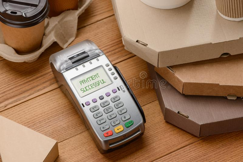 POS terminal among pizza boxes. And cups of coffee on wooden cash desk. Easy cashless payments by card or phone stock photos