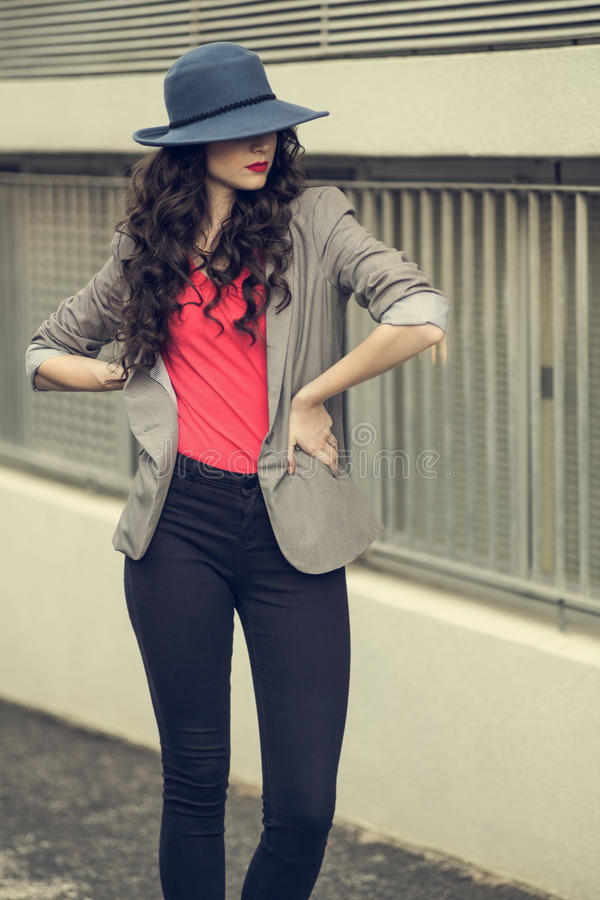 Posa alla moda d'uso castana affascinante attraente dei vestiti immagine stock libera da diritti