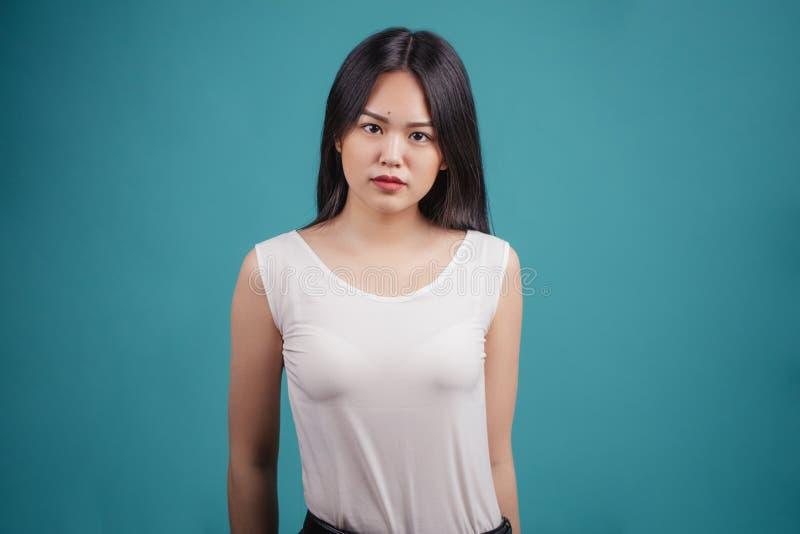 Posa asiatica attraente della donna isolata su fondo blu immagini stock