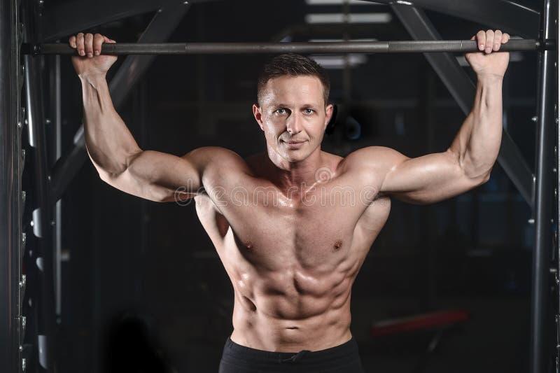 Posa atletica bella e treni dell'uomo di forma fisica nella palestra fotografia stock libera da diritti