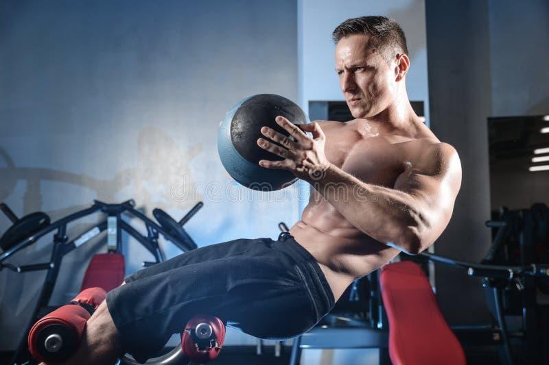 Posa atletica bella e treni dell'uomo di forma fisica nella palestra immagine stock