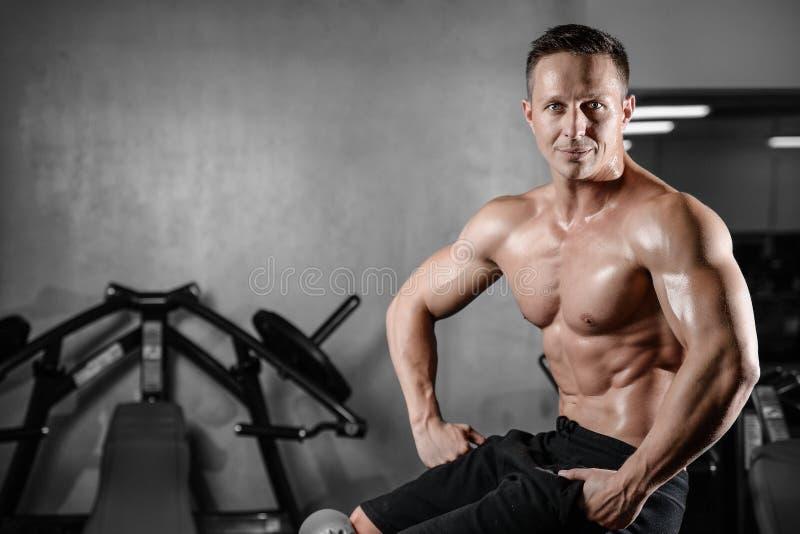 Posa atletica bella e treni dell'uomo di forma fisica nella palestra fotografia stock