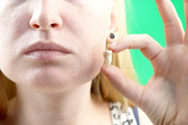 Posa confusa di una donna con mal di denti e di una mano che tiene il dente estratto, hocus sulla mano fotografie stock libere da diritti
