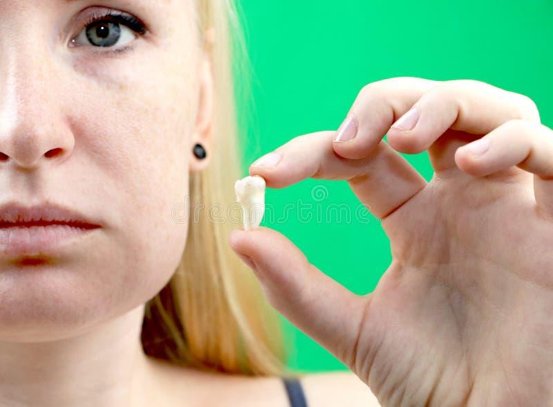 Posa confusa di una donna con mal di denti e di una mano che tiene il dente estratto, hocus sulla mano immagine stock libera da diritti