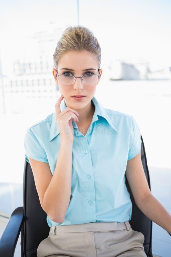 Posa d'uso di vetro della donna di affari pensierosa immagine stock