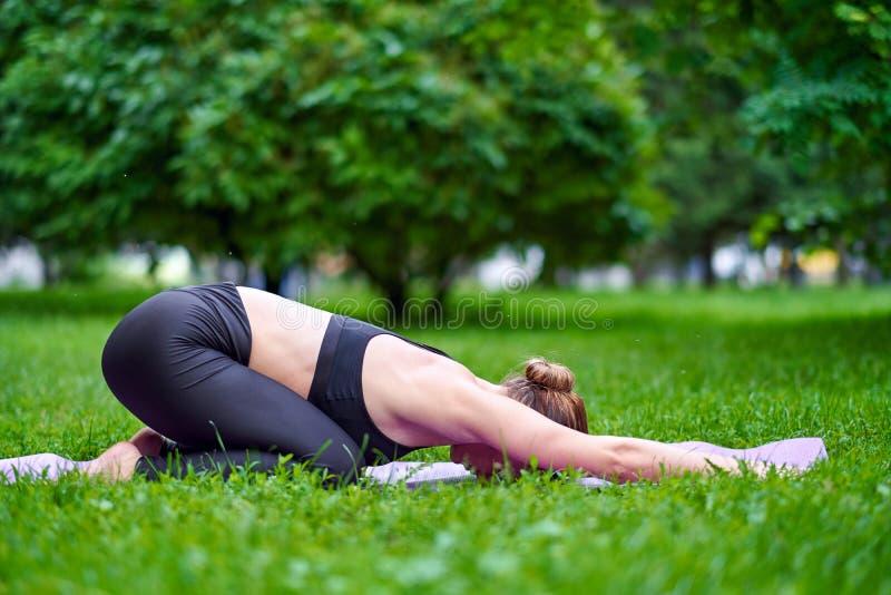Posa del bambino di yoga - Balasana Meditazione di pratica di yoga della giovane donna in natura al parco Concetto di stile di vi immagini stock