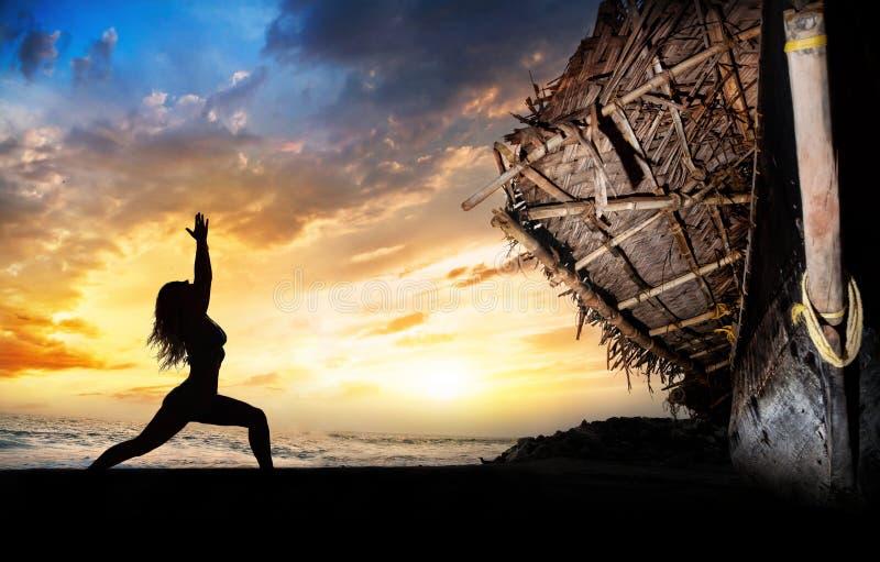 Posa del guerriero della siluetta di yoga vicino alla barca immagini stock libere da diritti