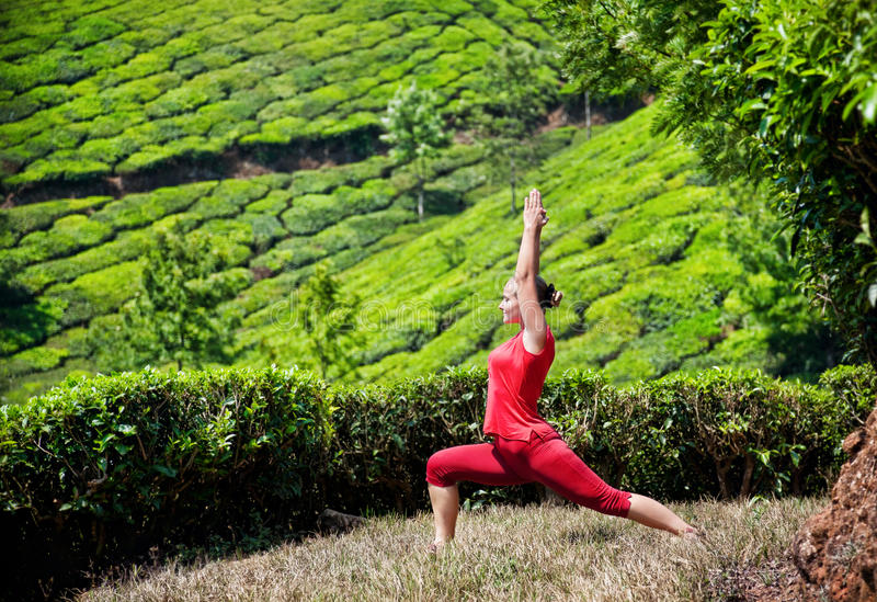 Posa del guerriero di yoga nelle piantagioni di tè immagini stock