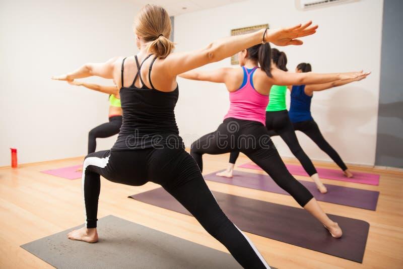 Posa del guerriero nella classe di yoga immagine stock libera da diritti