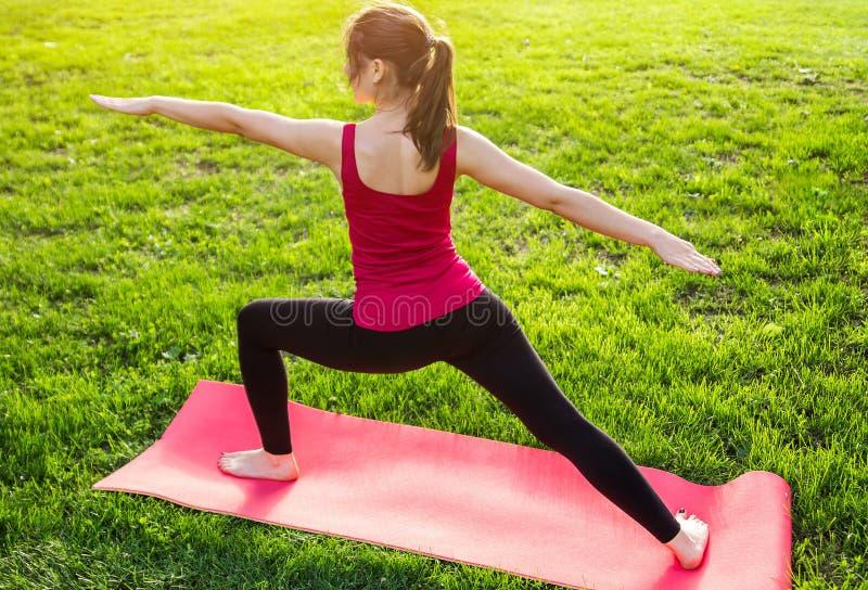Posa del guerriero yoga di pratica nel parco fotografia stock