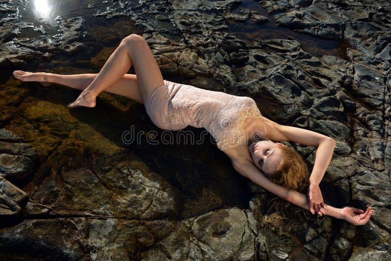 Posa del modello del costume da bagno sexy davanti al giacimento di lava nero fotografia stock