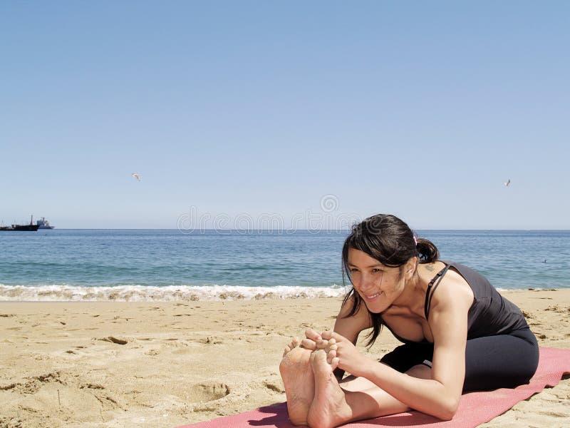 Posa del sit-up di yoga di Bikram alla spiaggia immagine stock