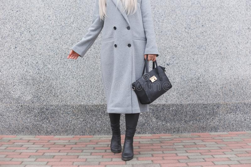 Posa della donna alla moda all'aperto, tenendo borsa di cuoio nera, stivali alla moda d'uso, cappotto elegante Concetto femminile fotografia stock