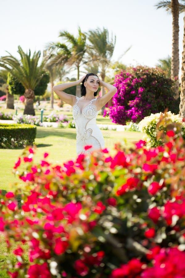 Posa della donna con i fiori sboccianti Modello di moda con capelli castana in giardino Ragazza di bellezza con lo sguardo di fas immagini stock libere da diritti