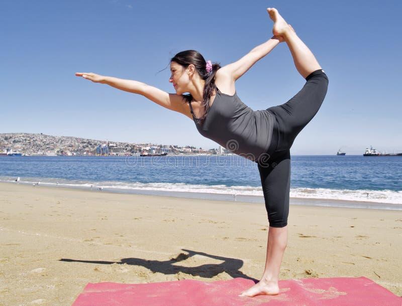 Posa di dhanurasana di dandayamana di yoga di Bikram alla spiaggia immagine stock libera da diritti