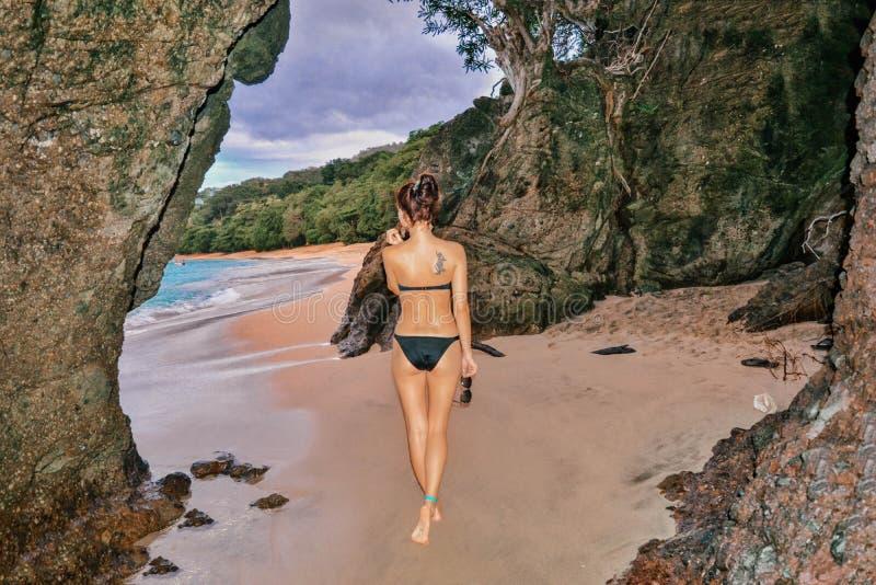 Posa di modello di bella forma fisica in una caverna sulla spiaggia fotografia stock