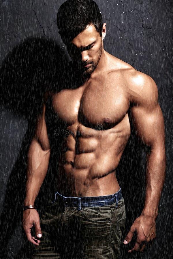 Posa di modello di forte forma fisica atletica bella sana dell'uomo vicino alla parete grigio scuro immagini stock