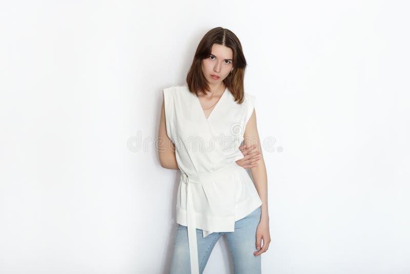 Posa di pratica della giovane bella del principiante donna castana del modello mostrando le emozioni sul fondo bianco dello studi immagini stock