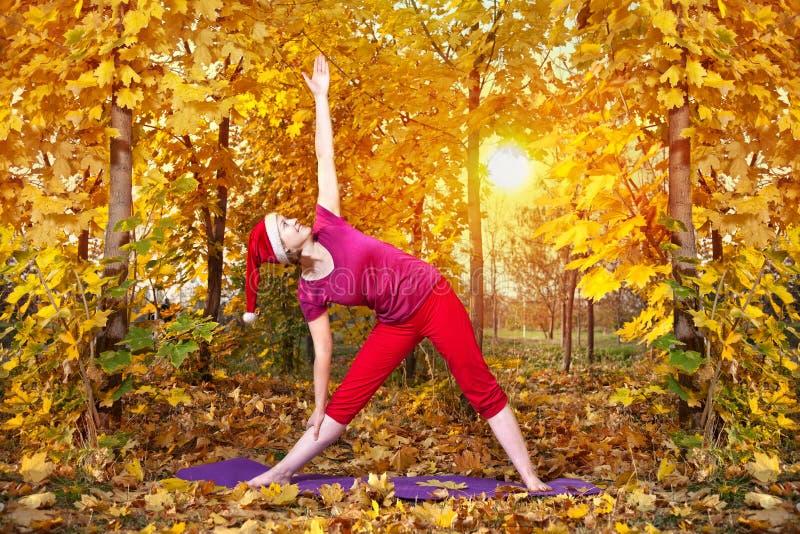 Posa di trikonasana di yoga di natale immagini stock