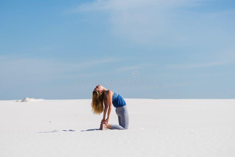 Posa di yoga del cammello di Ustrasana nel deserto fotografia stock