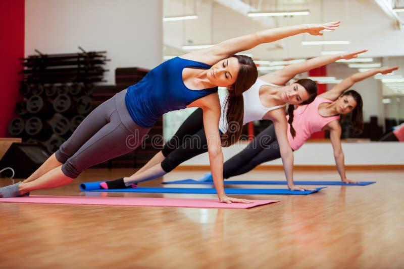 Posa di yoga della sponda da tre donne immagini stock libere da diritti
