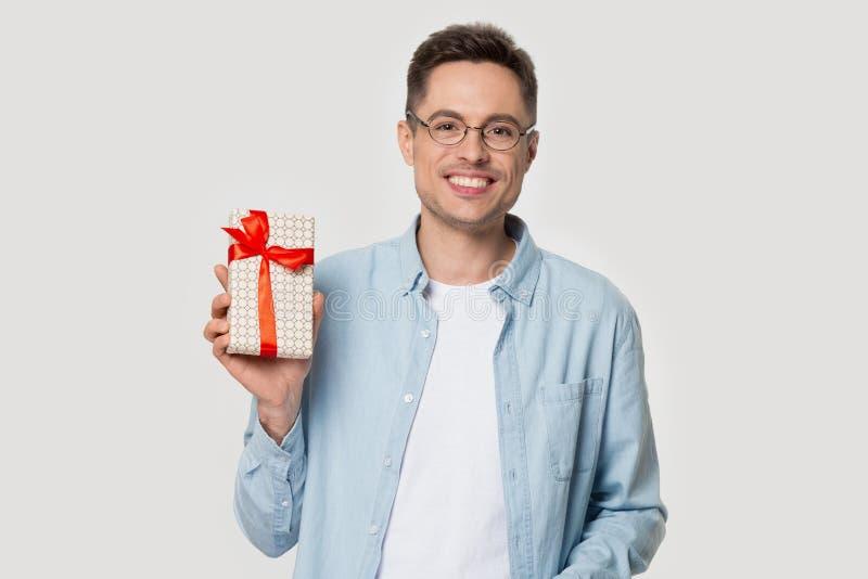 Posa felice del giovane sul contenitore di regalo grigio della tenuta del fondo dello studio fotografia stock
