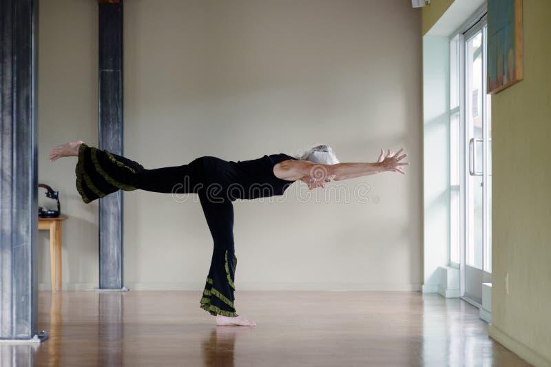Posa matura di yoga del guerriero III della donna immagini stock libere da diritti