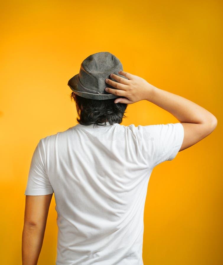 Posa posteriore dell'uomo asiatico confuso che tiene il suo Fedora d'uso capo fotografia stock libera da diritti