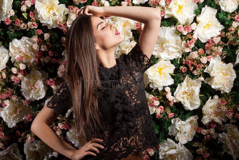 Posa romatic appassionata di signora sensuale sul fondo del fiore immagini stock
