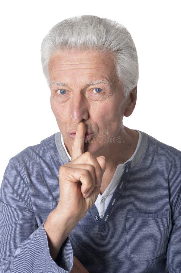 Posa senior e manifestazioni dell'uomo del ritratto un gesto di silenzio su fondo bianco immagini stock