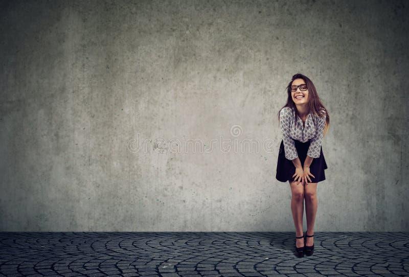 Posa sorridente del bello modello femminile esaminando macchina fotografica fotografia stock