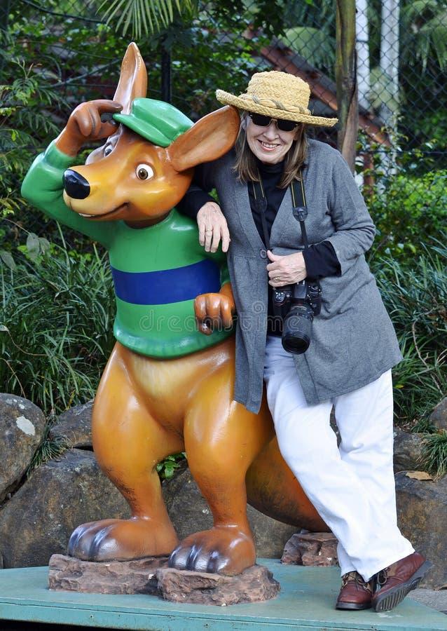 Posa turistica della donna con la statua la Gold Coast, Australia del canguro immagine stock