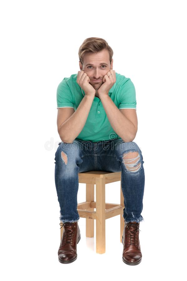 Posadzony śliczny mężczyzna jest dziecięcy z rękami przy twarzą obraz stock