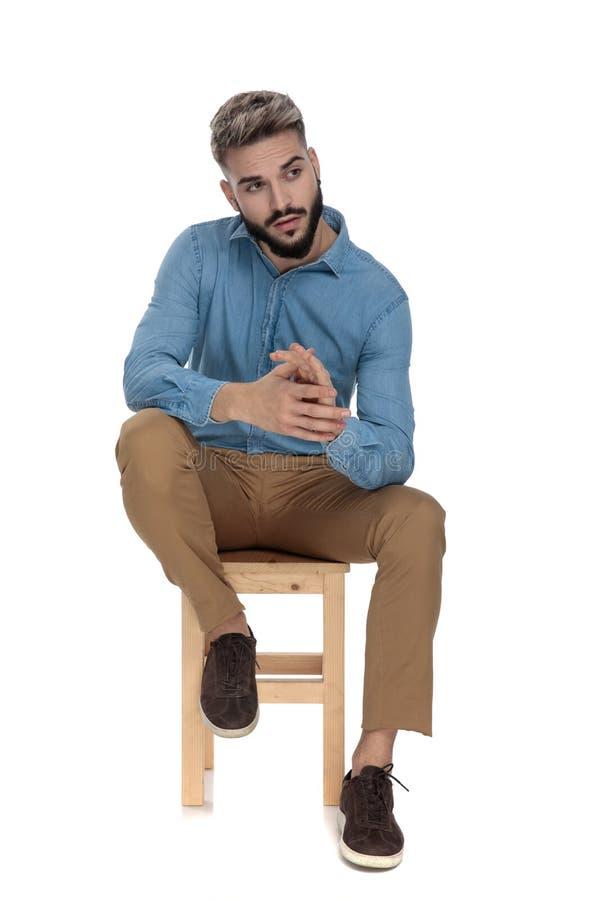 Posadzony czarujący mężczyzna patrzeje oddalony podczas gdy nacierający jego palmy obrazy stock
