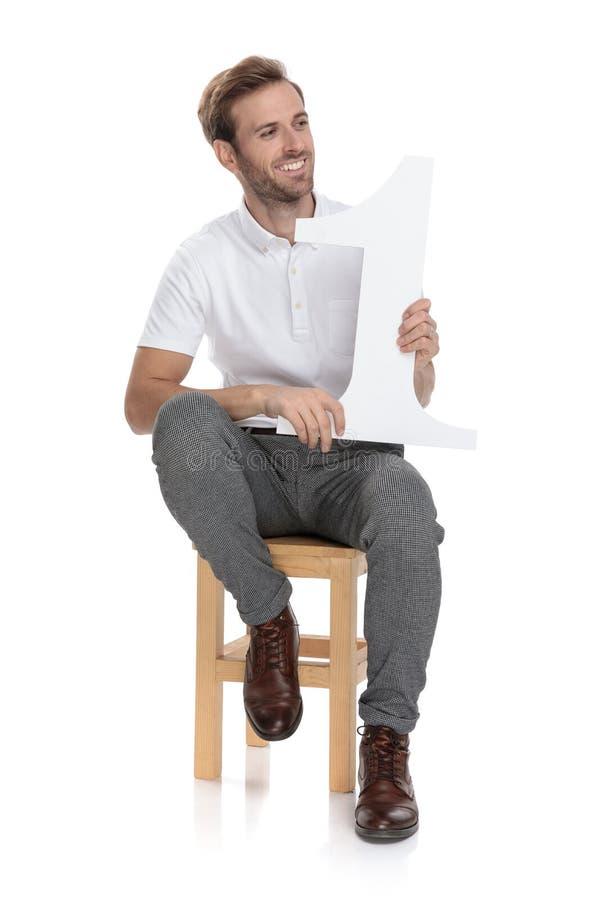 Posadzony mężczyzn chwytów liczby jeden list i spojrzenia popierać kogoś zdjęcie royalty free