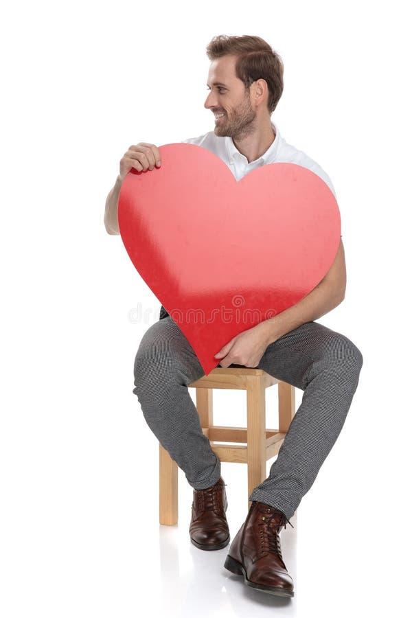Posadzony mężczyzna trzyma dużego czerwonego serce patrzeje daleko od obrazy stock