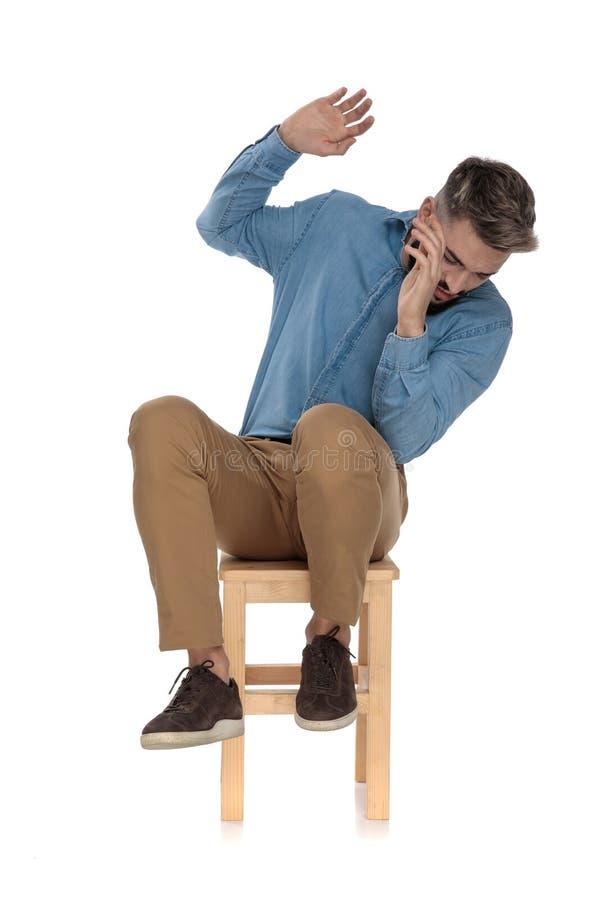 Posadzony straszący mężczyzna w niebieskich dżinsów koszulowy bronić z rękami zdjęcia stock