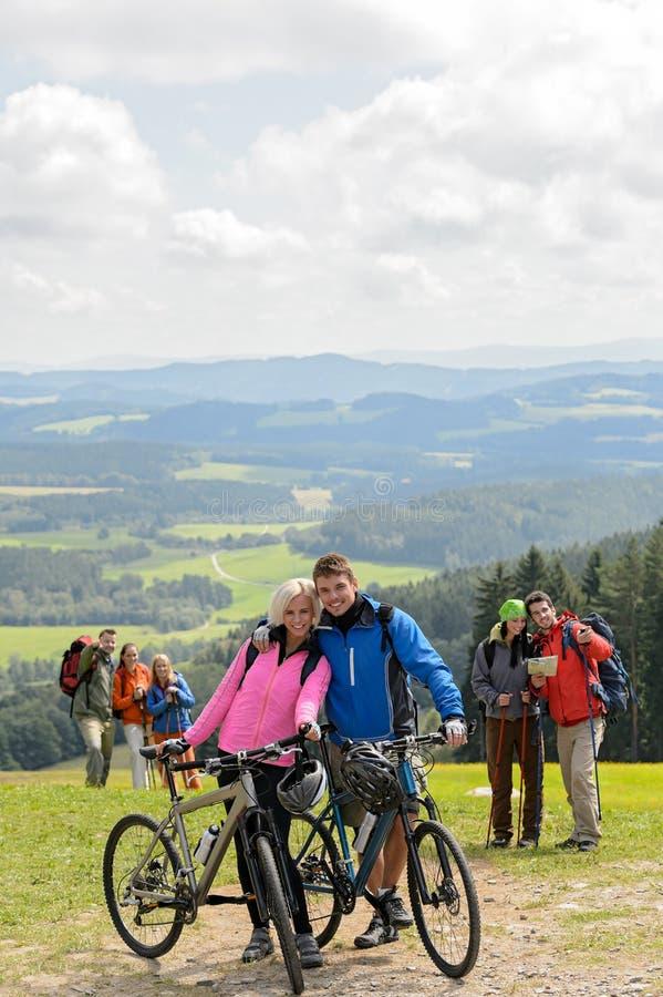 Pose des couples de cycliste sur la montagne avec des vélos photos libres de droits