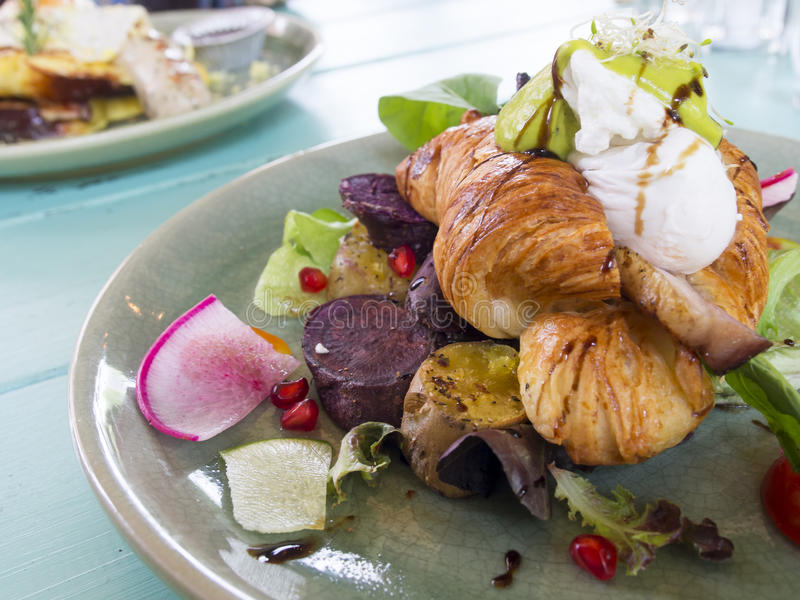 Poschiertes Ei auf Hörnchen mit geräuchertem Speck und Salat ärgert benedi stockfotos