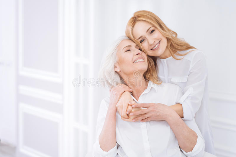 Posditive woman and her adult daughter resting at home stock photo