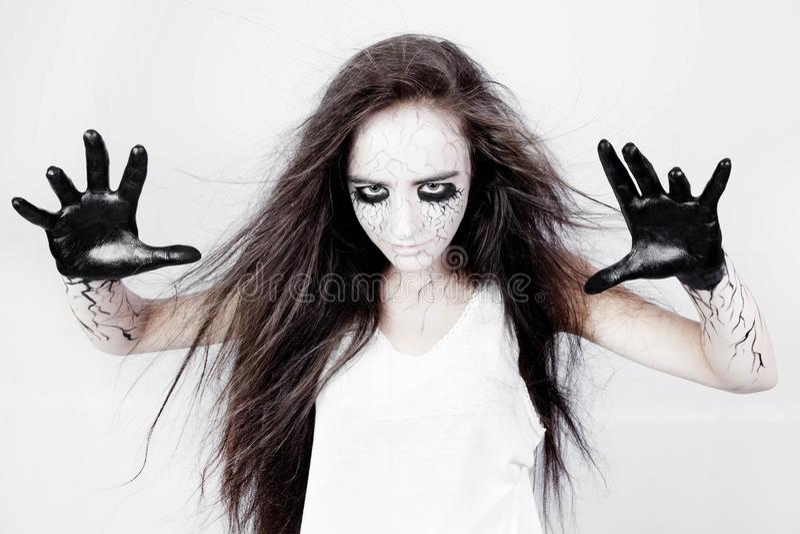 Poseído por bebidas espirituosas, una muchacha con las contusiones debajo de sus ojos y las venas del negro conjura sus manos con imagen de archivo libre de regalías