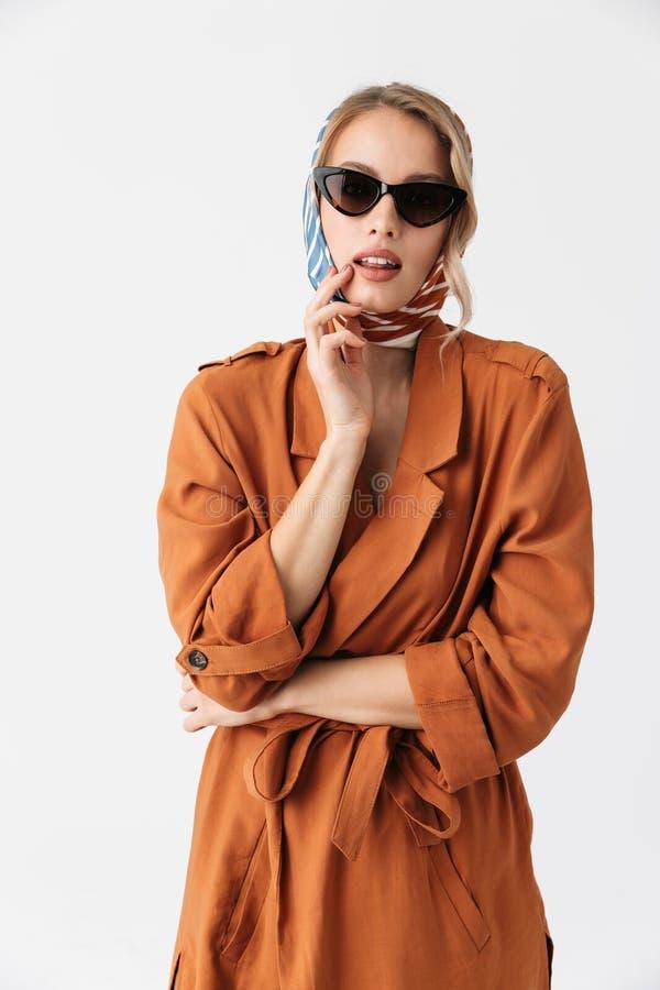 Pose élégante en soie de port d'écharpe de belle jeune femme d'isolement au-dessus des lunettes de soleil de port de fond blanc d photo libre de droits