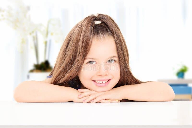 Pose adorable de petite fille posée à une table images libres de droits