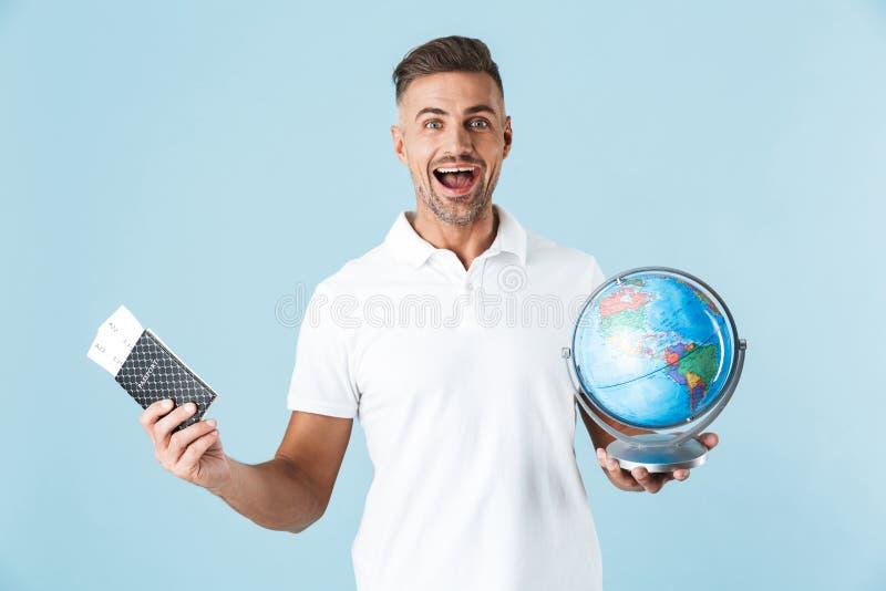 Pose adulte heureuse enthousiaste belle d'homme d'isolement au-dessus du passeport bleu de participation de fond de mur avec les  photo stock