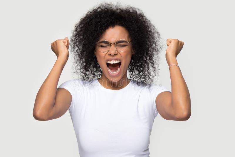 Pose africaine enthousiaste gaie heureuse de femme au-dessus de fond gris images stock