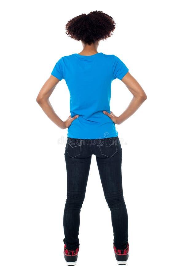 Pose arrière de jeune femme faisant face au mur photo stock