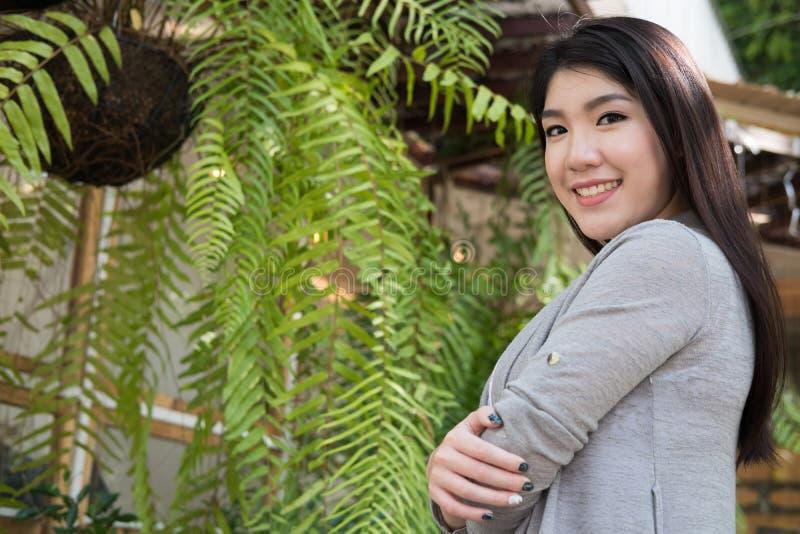 Pose asiática da mulher no café exterior adulto fêmea novo com natura imagem de stock royalty free