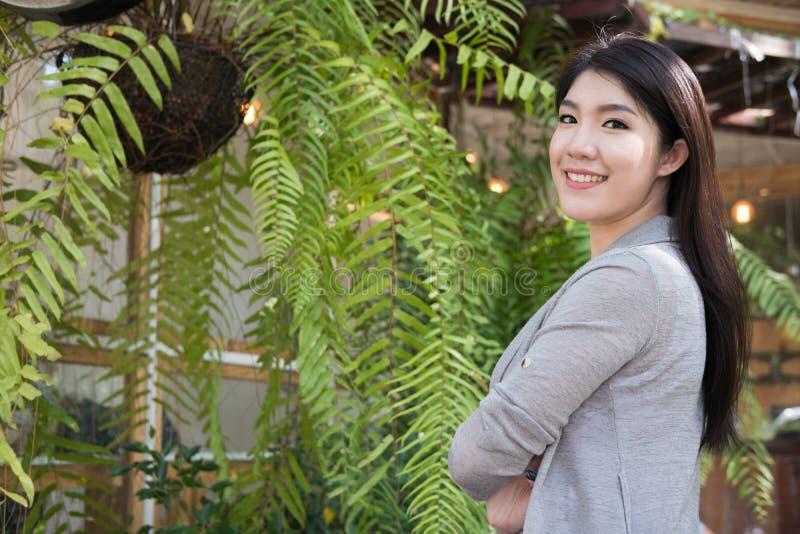 Pose asiatique de femme au café extérieur jeune adulte féminin avec le natura photos libres de droits