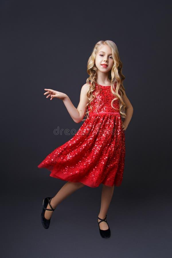 Pose blonde de petite fille dans le studio sur le fond noir photo libre de droits