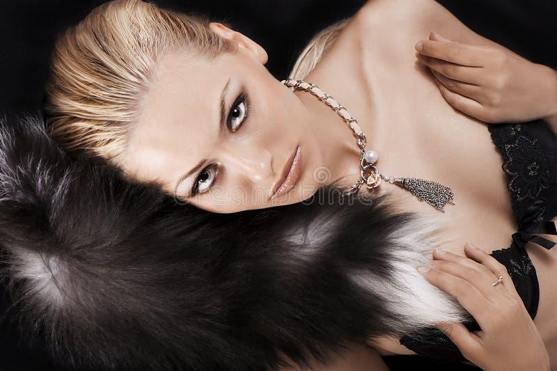 Pose blonde sexy sur le noir s'usant juste la fourrure photos libres de droits